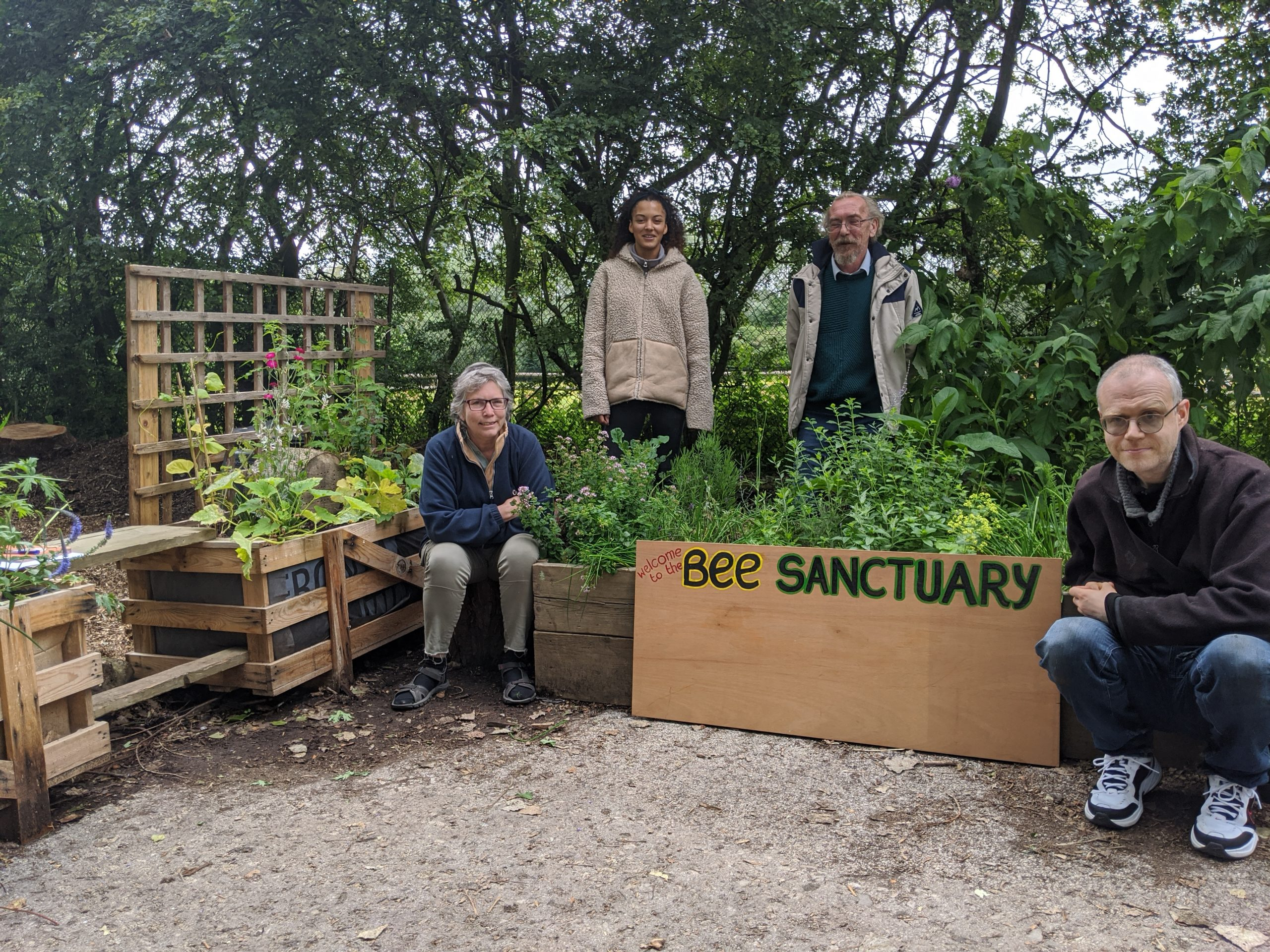 Volunteers with welcome sign and planters