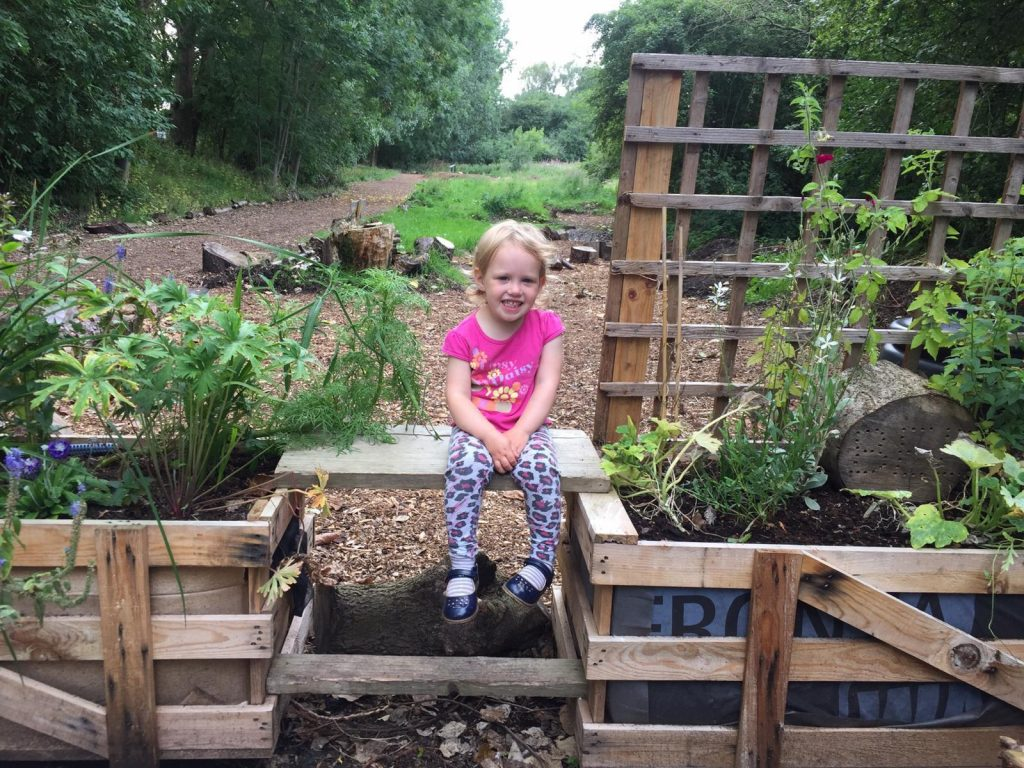 Little girl sits on bench between planters